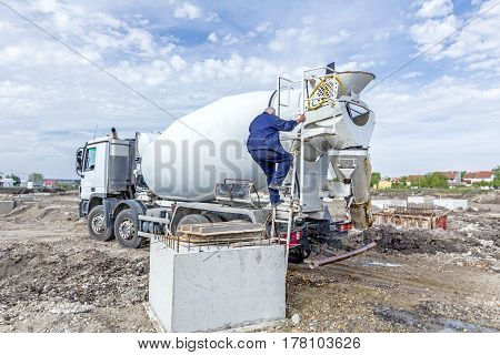 Driver is washing mixer truck with water jet after concrete casting.