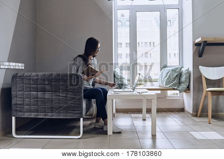 Paying attention to every detail. Beautiful young woman holding a book and a cup while looking at the laptop