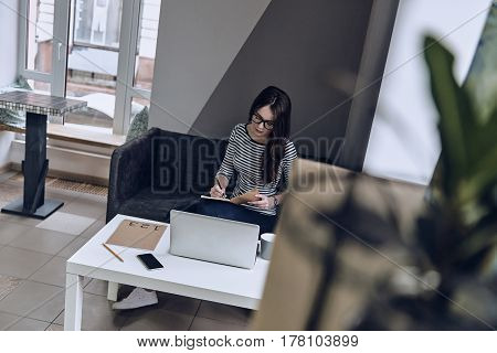 Writing down her thoughts. Top view of thoughtful young woman writing something down in her notebook while sitting on the sofa at her working place