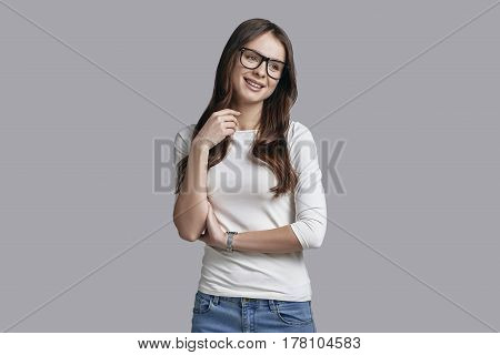 Beautiful daydreamer. Attractive young woman in thick rimmed glasses looking away with a smile while standing against grey background
