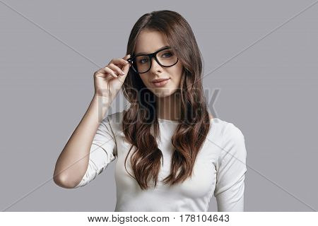 Girl of your dreams. Attractive young woman adjusting her thick rimmed glasses and looking at camera with a smile while standing against grey background