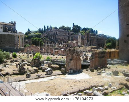 Roman Forum in Rome city center in Italy - historical plaza with ruins of ancient government buildings and modern travel path for tourists. Famous roman monument with blue sky background