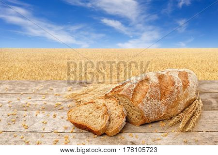 sliced whole grain bread with dry ears of wheat on a wooden table with golden field on the background. Fresh baked traditional bread on nature background