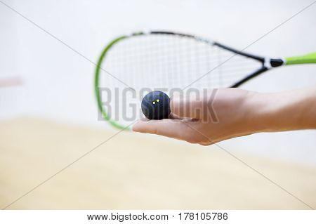 squash racket and ball in man's hands. Racquetball equipment. Photo with selective focus. Player prepares to serve a ball. Closeup of male hand serving ball