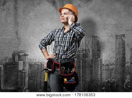 Engineer woman with cellphone and sketches of construction project on wall