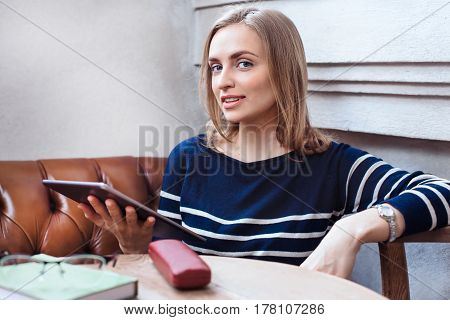 Beautiful young woman sitting in cafe and use tablet. Smiling and looking at camera. Consept of studing and working online. Beautiful woman with digital tablet while relaxing after work