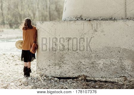 Stylish Boho Woman Posing At River Under Stone Bridge, Back View. Beautiful Gypsy Girl With Hat And