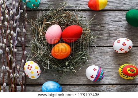 Handmade easter diy painted eggs in hay nest on wood background. Colorful holiday decoration on rustic table top view