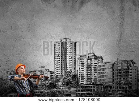 Engineer woman playing violin and sketches of construction project on wall