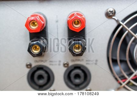 Close Up Of Rear End Of Music Amplifier. Black and Red Audio Output