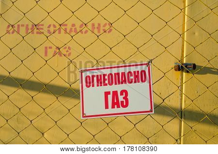 Warning sign on the fence of a metal mesh
