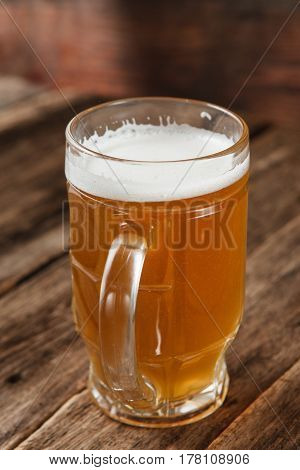 Mug with cold light beer on rustic wooden table in pub, close up view. Handmade craft drink, summer refreshment, brewery concept