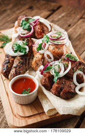 Mixed grilled meat on wooden board. Assorted delicious bbq served on pita bread with herbs, onion, and tomato sauce. Menu photo.