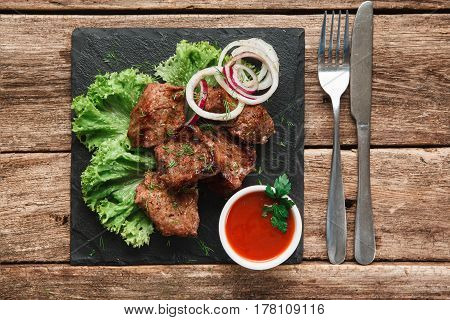 Delicious shashlik served with salad and onion rings on black slate with tomato sauce and cutlery, top view. Menu photo.
