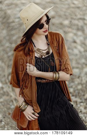 Beautiful Stylish Boho Woman In Sunglasses And Hat, Fringe Poncho And Leather Bag. Hipster Girl In G