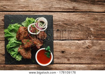 Appetizing grill meal decorated with onion rings and lettuce salad on black slate with tomato sauce, on rustic wooden table with free space. Restaurant menu photo.