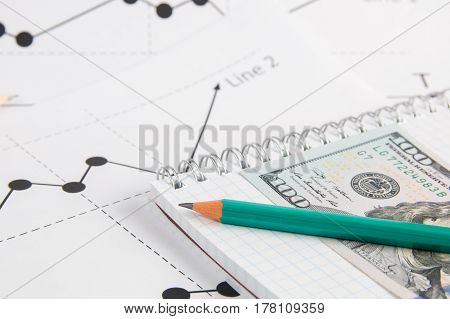 Business drawing graphics pancil 100 usa dollars banknote and white notepad