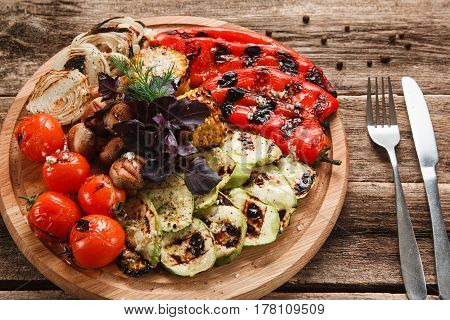 Tomatoes, red pepper, onion, zucchini, corn and mushrooms decorated with basil, served with cutlery. Restaurant menu photo Healthy lifestyle, vegetarian cuisine concept
