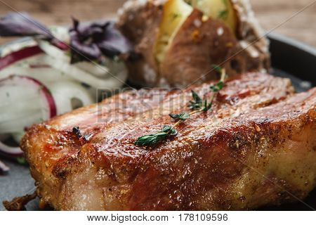 Juicy grilled beef steak decorated with herbs, served with baked potato and onion rings, close up view. American cuisine. Menu photo.