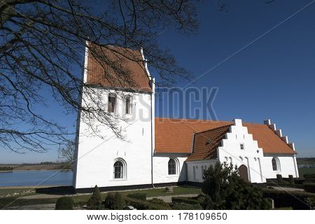 Old traditional Danish white village church in Fons on Funen.