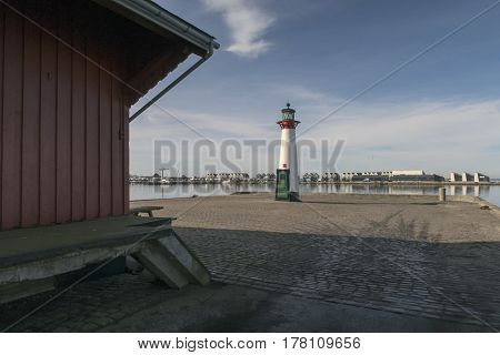 Old red and white lighthouse on Assens harbor in Denmark