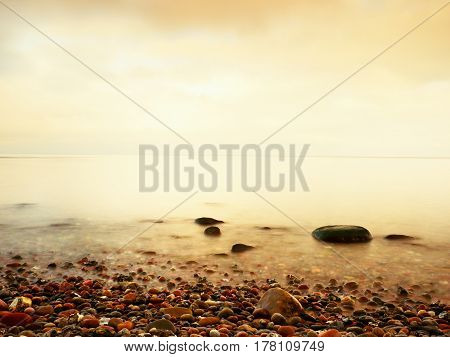 Stony Beach In Island In Romantic Colors Of Tropical Sunset