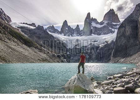 man in red t-short standing near blue lake in patagonia, fitz roy mountain at sunset