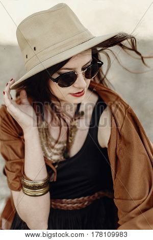 Beautiful Stylish Hipster Woman In Sunglasses Holding Hat, With Windy Hair. Boho Traveler Girl In Gy