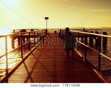 Alone Tourist Takes Photos With Camera And Tripod On Wooden Pier