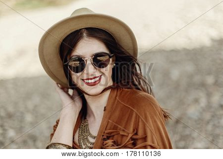 Stylish Boho Woman Smiling In Sunglasses Holding Hat, With Windy Hair. Hipster Girl In Gypsy Look, Y