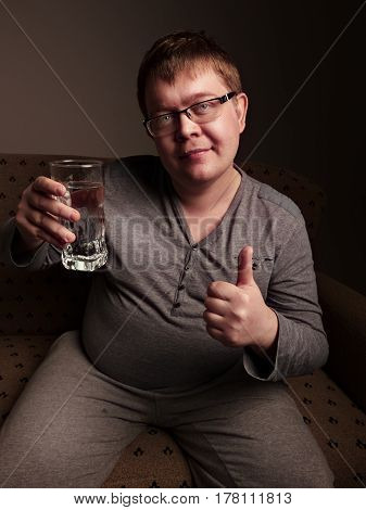 Overweight man drinking water while showing thumb up