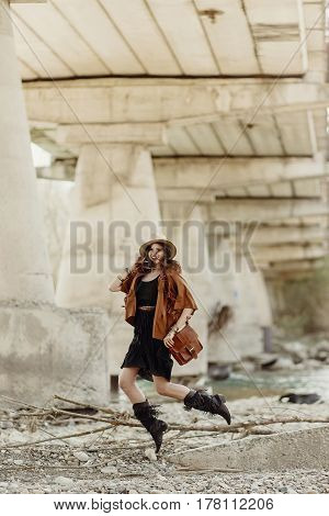 Stylish Boho Woman Jumping, Having Fun, In Hat, Leather Bag, Fringe Poncho And Boots  Near River Und