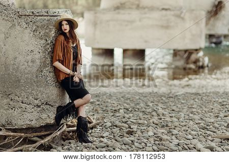 Stylish Boho Woman With Jewelry Posing At Rock Wall. Beautiful Gypsy Dressed Girl With Hat And Fring