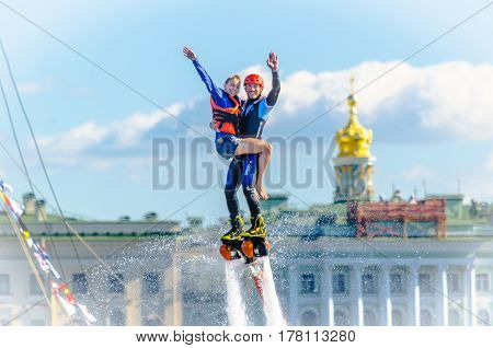 Athlete flybarless with devochkoy on hand against the blue sky and clouds privetstvuet the public on the embankment of the river Neva. Russia, Saint-Petersburg, August 15, 2015.