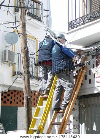 Men Working On Solving Cabeling Problem
