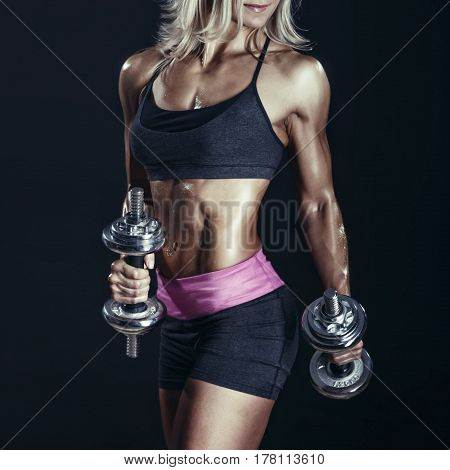 Fitness young woman standing with dumbbells on dark background. Female bodybuilder in sports clothing ready for gym exercise with dumbbells.