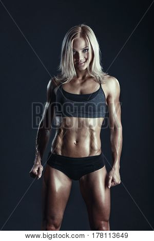 Fitness young woman standing on dark background. Muscular female looking at camera. Female bodybuilder in sports clothing ready for gym exercise.