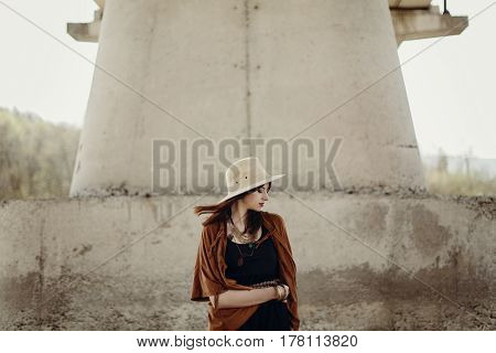 Stylish Hipster Woman In Hat With Windy Hair Posing Near River Stones. Boho Traveler Girl In Gypsy L