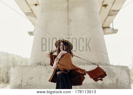 Stylish Hipster Woman Having Fun, In Hat With Windy Hair Near River Stones. Boho Traveler Girl In Gy