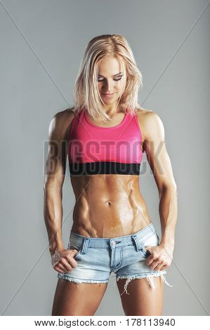 Beautiful young sporty muscular woman looking on her abdominal Press