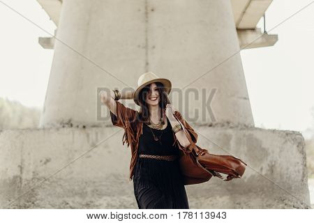 Stylish Hipster Woman Having Fun And Smiling, In Hat With Windy Hair Near River Stones. Boho Travele