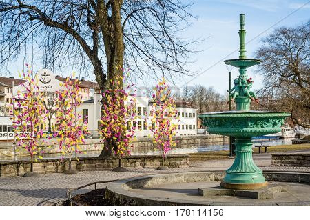 UPPSALA SWEDEN - Mar 26 2016 - Street view of inactive fountain with traditional colourful feathers on trees for Easter decorations in Uppsala Sweden Europe