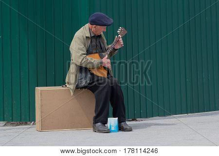 Kiev Ukraine - May 03 206: An elderly man makes a living playing a balalaika