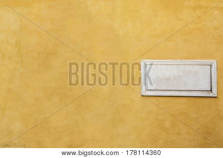 White Marble Classic Blank Nameplate With Empty Space For Text And Numbers On Yellow Painted Wall Of
