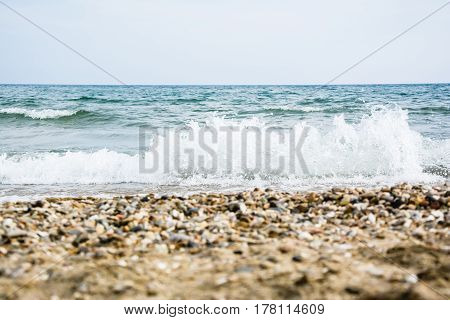 Brown Pebble (small Stones) In The Foreground With Blurred Sea Tidal Waves, Splash And The Horizon L