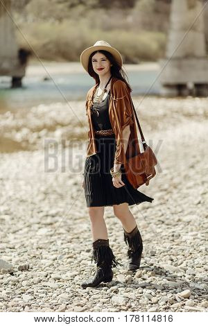 Stylish Hipster Woman In Hat, Fringe Poncho And Boots Walking On River Beach. Boho Traveler Girl In