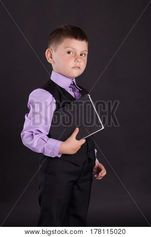 Child with a book. Boy in a suit with tie.