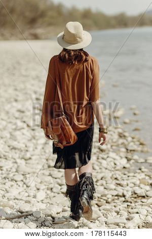 Stylish Boho Gypsy Woman In Hat, Fringe Poncho And Boots Walking On River Beach,back View. Hipster T