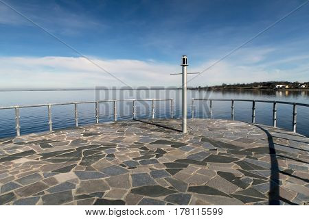 ASSENS DENMARK - MARCH 24 2017: Very small lighthouse at the end of the modern designed walkway on pier a springtime day close to the sea. March 24 2017 Assens Funen Denmark.
