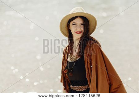 Stylish Boho Traveler Woman In Hat, Fringe Poncho Posing Near Water River Beach, Gypsy Hipster Girl